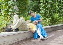 Det unga lyckliga paret sitter i berså tvinnade gräsplanerna Fotografering för Bildbyråer