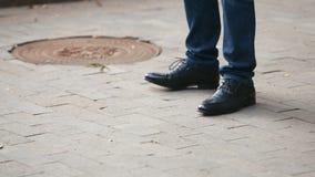 Det unga manliga affärsparet väntar på ett möte Lägger benen på ryggen närbild vänte lager videofilmer