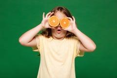 Det unga nätta flickanederlaget synar med apelsiner över grön bakgrund arkivfoton