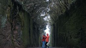 Det unga optimistiska paret som rymmer händer, går och vänder på en tunnelväg mellan vaggar omkring täckt av träd i Anaga stock video