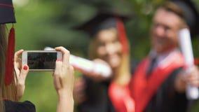 Det unga paret av universitetet avlägger examen att krama och att posera för fotoet, tummar-upp lager videofilmer