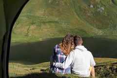 Det unga paret kramar sig framme av ett tält i bergen av Schweiz arkivfoto