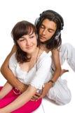 Det unga paret lyssnar till musik i hörlurar Royaltyfri Bild