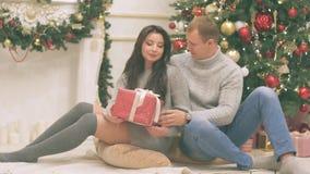 Det unga paret som är förälskat i dekor för nytt år med gåva- och julträdet, där är oväsen i videoen arkivfilmer