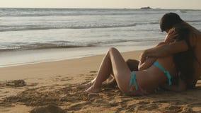 Det unga romantiska paret tycker om sammanträde för härlig sikt på stranden och krama En kvinna och en man sitter tillsammans in arkivfoton