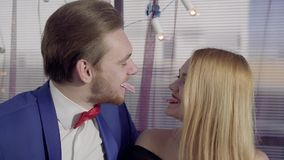 Det unga smiley lyckliga paret som har inom dem tänder som viker kortet och blont trycka på för kvinna, mans kortet på hans mun m stock video