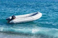Det uppblåsbara fartyget med en motor svänger på havsvågor nära kusten Royaltyfria Foton