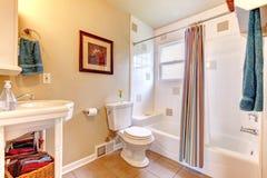 Det uppfriskande badrummet med vit badar och det beigea tegelplattagolvet Arkivfoton