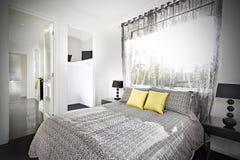 Det upplysta sovrummet med en modell planlade sängarket Arkivbild