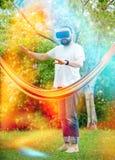 Det uppsökte barnet man bärande virtuell verklighetskyddsglasögon som har gyckel i hans trädgård Gyckel för livsstilen VR och kop Arkivfoton