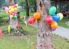 Det utomhus- partiet i trädgård dekorerade med färgrika ballonger Arkivbild