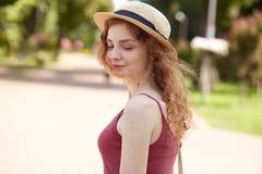 Det utomhus- skottet av den fundersamma attraktiva unga damen med ganska lockigt hår och att posera in parkerar och att ha sommar arkivbild