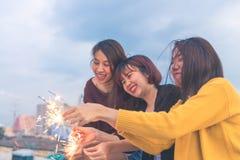 Det utomhus- skottet av ungdomarpå taket festar Den lyckliga gruppen av asia flickavänner tycker om och spelar tomteblosset på ta royaltyfri bild