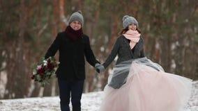 Det utomhus- vinterskottet av ung bröllopparspring och att ha roliga innehavhänder i snö rider ut pinjeskogen under