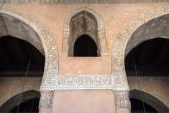 Det välvda fönstret mellan två bågar dekorerade med blom- modeller på Ibn Tulun den historiska moskén, Kairo, Egypten Royaltyfri Bild