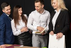 Det vänliga bisinesslaget har arbete i kontoret genom att använda bärbara datorn på tabellen arkivbild