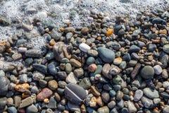 Det våta ljusa skinande kulöra kiselstenstenar och havet skummar Arkivfoton