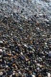 Det våta ljusa skinande kulöra kiselstenstenar och havet vinkar Arkivbild
