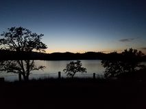 Det varma glödet av solnedgången över att lugna vatten arkivfoton