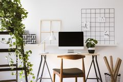 Det verkliga fotoet av träskrivbordet med metalllampan, den nya växten och tömmer skärmbildskärmanseende i vitlägenhetinre fotografering för bildbyråer