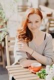 Det vertikala skottet av den attraktiva röda haired unga kvinnan med krabbt hår, iklätt varmt förkläde, dricker kaffe, eller latt royaltyfri foto