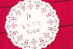 Det vit dekorerade stycket av papper på röd träyttersida med handstilen älskar jag dig Arkivfoton