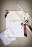 Det vita bröllopkortet med bandet och papper snör åt Stearinljus med band Royaltyfria Bilder