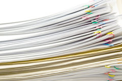 Det vita dokumentet och paperclipen förlägger växling med det bruna kuvertet Arkivfoto