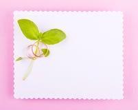 Det vita hälsningkortet med den krabba kanten dekoreras med vigselringar och gräsplanplan på rosa bakgrund Royaltyfria Foton