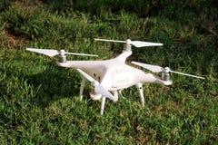 Det vita quadcoptersurret med 4K som den digitala kameran på gräs är klar för, tar av till flugan i luft för att ta foto, rekord- Arkivfoton