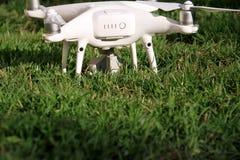Det vita quadcoptersurret med 4K som den digitala kameran på gräs är klar för, tar av till flugan i luft för att ta foto, rekord- Royaltyfri Fotografi