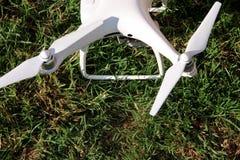 Det vita quadcoptersurret med 4K som den digitala kameran på gräs är klar för, tar av till flugan i luft för att ta foto, rekord- Arkivbilder