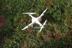 Det vita quadcoptersurret med 4K som den digitala kameran på gräs är klar för, tar av till flugan i luft för att ta foto, rekord- Fotografering för Bildbyråer