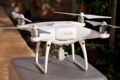 Det vita quadcoptersurret med 4K som den digitala kameran på ställning är klar för, tar av till flugan i luft för att ta foto, re Arkivfoto