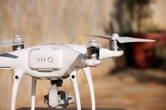 Det vita quadcoptersurret med 4K som den digitala kameran på ställning är klar för, tar av till flugan i luft för att ta foto, re Royaltyfria Bilder