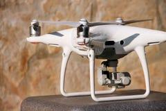 Det vita quadcoptersurret med 4K som den digitala kameran på ställning är klar för, tar av till flugan i luft för att ta foto, re Arkivbild