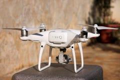 Det vita quadcoptersurret med 4K som den digitala kameran på ställning är klar för, tar av till flugan i luft för att ta foto, re Arkivfoton