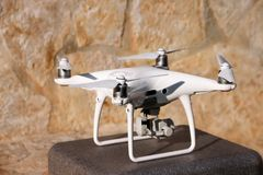 Det vita quadcoptersurret med 4K som den digitala kameran på ställning är klar för, tar av till flugan i luft för att ta foto, re Arkivbilder