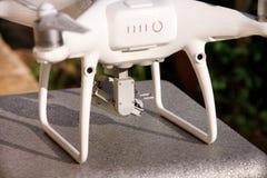 Det vita quadcoptersurret med 4K som den digitala kameran på ställning är klar för, tar av till flugan i luft för att ta foto, re Royaltyfri Foto