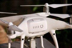 Det vita quadcoptersurret med 4K som den digitala kameran på ställning är klar för, tar av till flugan i luft för att ta foto, re Fotografering för Bildbyråer