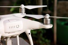 Det vita quadcoptersurret med 4K som den digitala kameran på ställning är klar för, tar av till flugan i luft för att ta foto, re Royaltyfri Fotografi