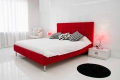 Det vita rummet med en röd säng arkivfoton