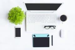 Det vita skrivbordkontoret med bärbara datorn, smartphonen och annan arbetar supplie Fotografering för Bildbyråer
