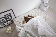 Det vita sovrummet. Kvinna som sover på sängen. Arkivbild