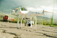 Det vita surret med kameran monterade under sammanträde på konkret yttersida, berglandskapbakgrund Arkivfoton