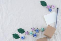 Det vita tomma kortet, pennan och bruntgåvaasken dekorerar med pappers- blommor för blåttsignalen royaltyfri foto