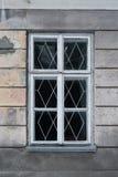 Det vita träfönstret med spisgallret i ett av gatahusen Royaltyfria Foton