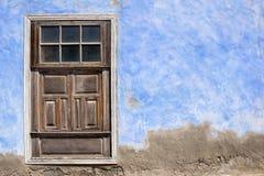Det Wood fönstret med slutare stängde sig på en blått- och grå färgvägg Royaltyfri Bild