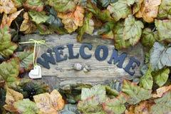 Det Wood välkomna tecknet med hjärtor och höstsidor gränsar att hänga på dörr Royaltyfri Foto