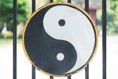 Det Ying och Yang symbolet hänger på porten av en Taoisttempel i haka Arkivfoto